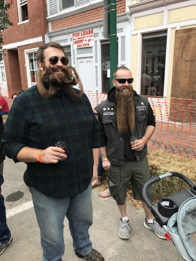Bryce Royal, left, and Zachary LeClair talk with other members of the Maine Facial Hair Club on Saturday afternoon during the eighth annual Swine & Stein Oktoberfest in Gardiner.