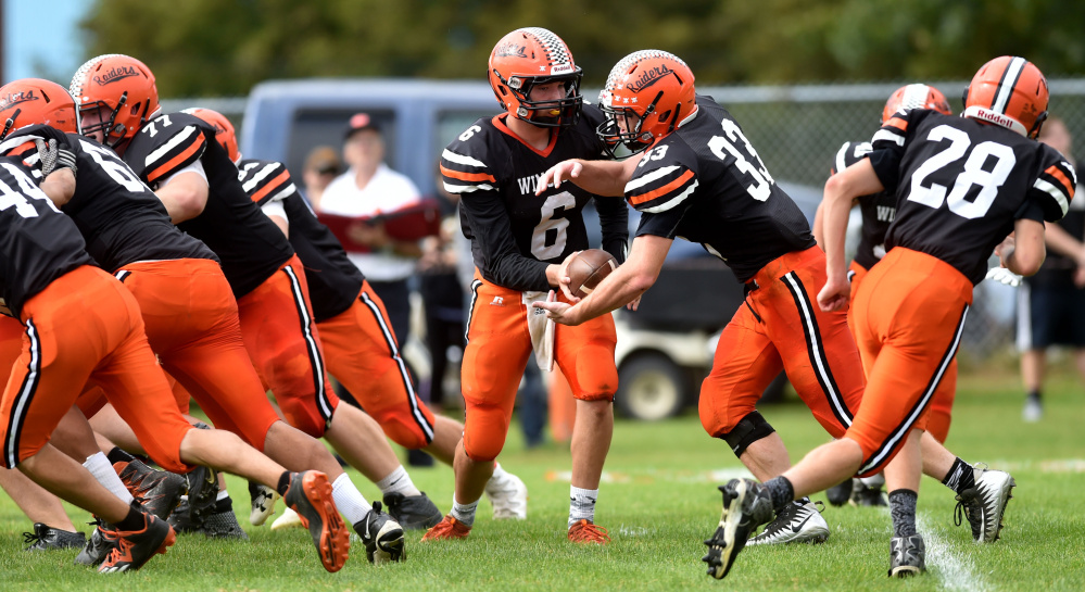 Winslow High School quarterback Ryan Gagnon (6) hands the ball off to Ryan Fredette (33) against Gardiner on Saturday in Winslow.