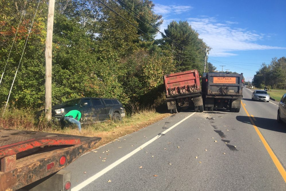 Two dump trucks got stuck together when they veered into the oncoming lane one after the other to avoid a trash truck in their lane. In the process the first forced the driver of a Toyota pickup off the road and into a utility pole.