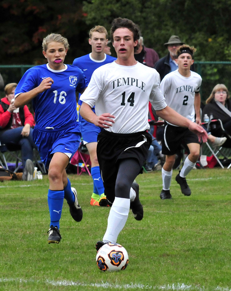 Temple Academy's Noah Shepherd races up field as Chop Point defender Josie Harrington pursues during a game Wednesday in Waterville.