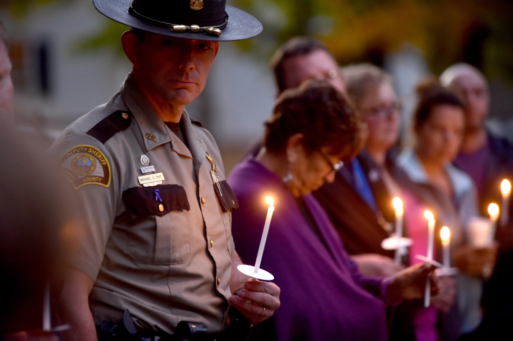 Michael Pike a domestic violence investigator with the Somerset County Sheriff's Office holds a candle Thursday during a domestic violence awareness candlelight vigil at the gazebo at Coburn Park on Water Street in Skowhegan