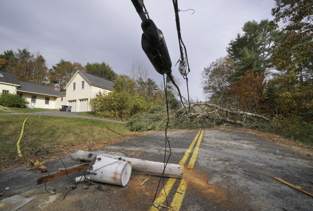 A utility pole with a transformer attached still lies in the middle of Flying Point Road in Freeport, under wires weighted down by trees that block the road, on Nov. 3. The storm that caused the damage left nearly 500,000 Maine electricity customers without power.