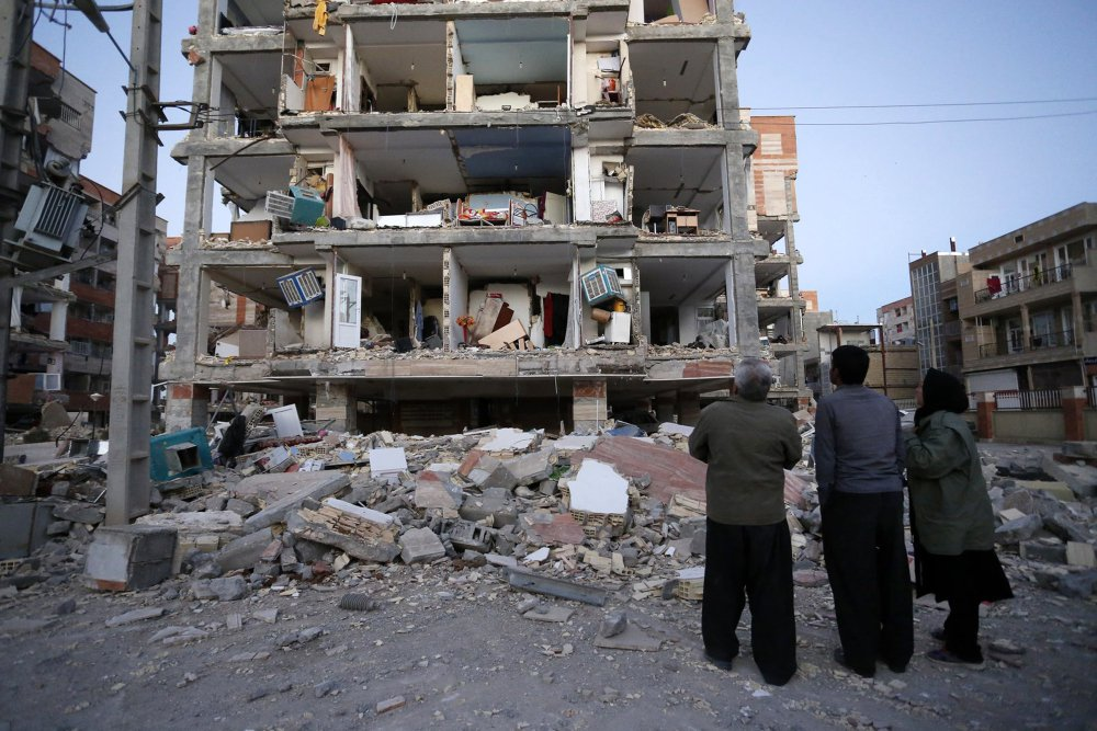 People look at destroyed buildings after an earthquake at the city of Sarpol-e-Zahab in western Iran.