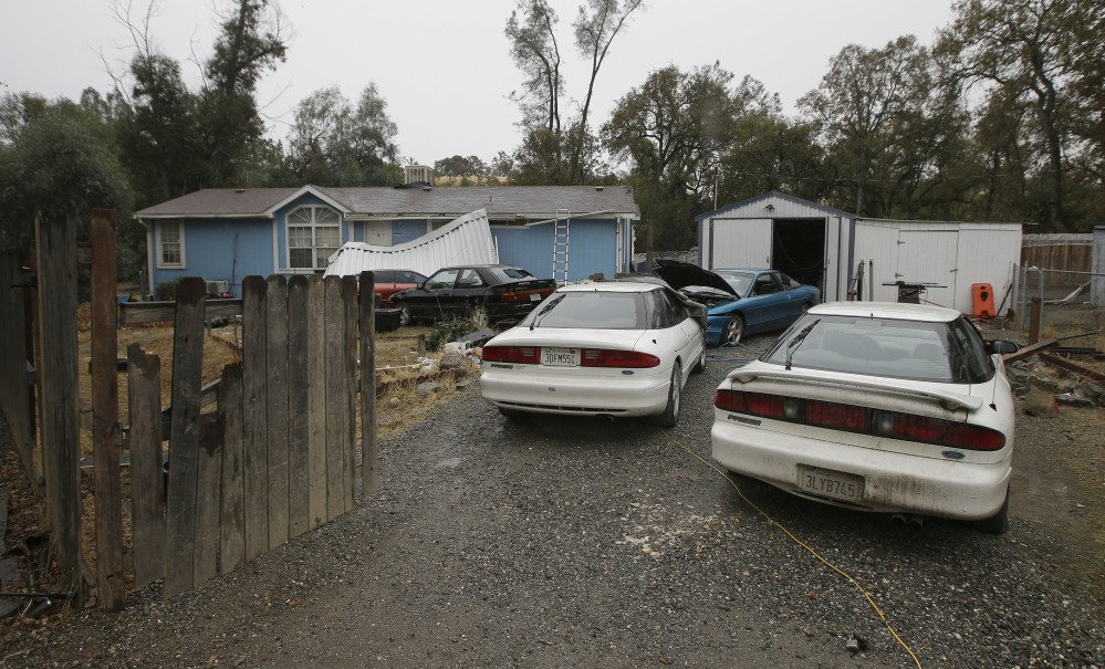 Cars are parked in front of the home of Kevin Janson Neal on Wednesday in Rancho Tehama Reserve, Calif. The body of Neal's wife was found at the home, where Neal started his shooting rampage that left four others dead, before he was shot and killed by Tehama County Sheriff's deputies.