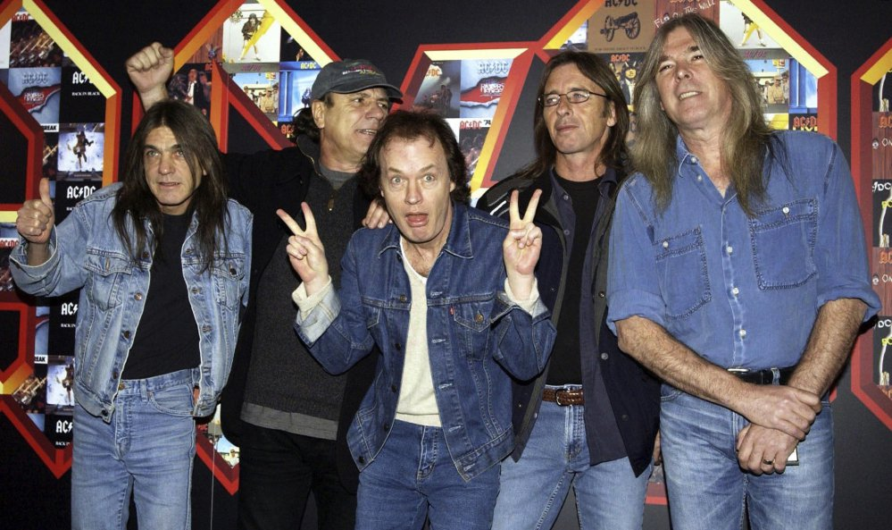 The members of AC/DC, Malcolm Young, from left, Brian Johnson, Angus Young, Phil Rudd and Cliff Williams, pose in 2003 at the Apollo Hammersmith in London.