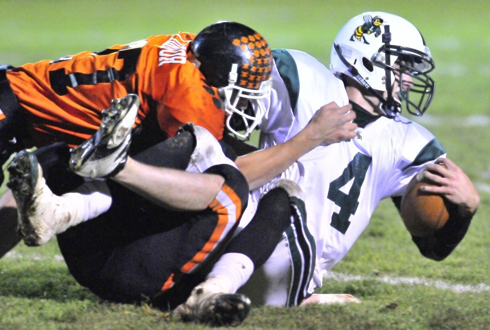 Staff file photo by Joe Phelan   Gardiner defensive back Alonzo Connor, left, and Nathan Lapointe, bottom, wrap up Leavitt quarterback Jordan Hersom during a 2010 game at Hoch Field in Gardiner. Hersom is now an assistant coach at Gardiner.