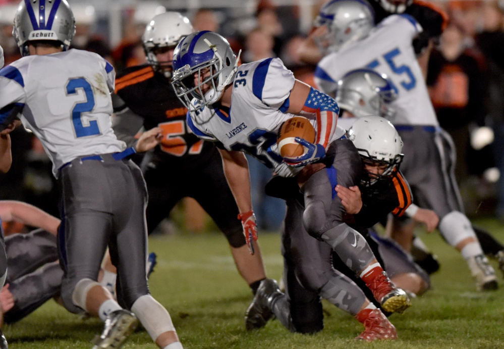 Lawrence running back Tyler Larouche (32) gets tackled by Skowhegan defender Kobe Houghton during a Pine Tree Conference Class B game earlier this season at Clark Field in Skowhegan.