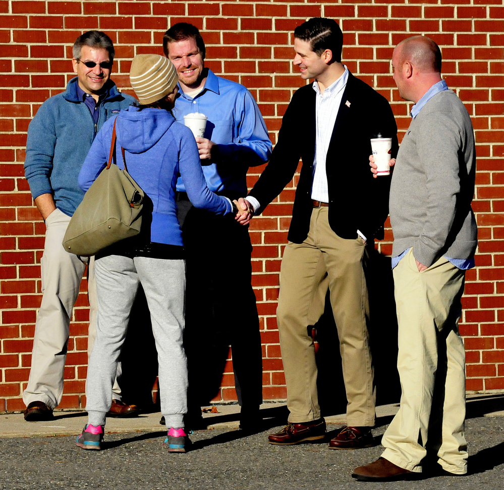 Waterville mayoral candidates, from left, John Levesque, Erik Thomas and Nick Isgro and Ward 4 City Council candidate Chris Rancourt greet Waterville voters Tuesday at the Thomas College polling place.