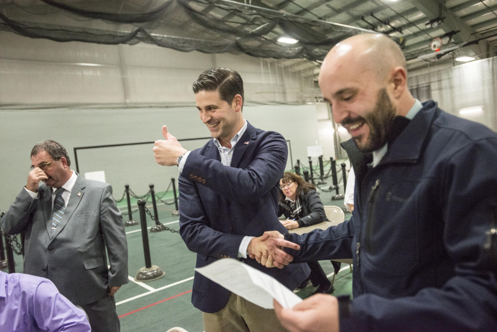 Nick Isgro gives a thumbs-up after hearing the results of the Waterville mayoral race Tuesday at Thomas College in Waterville as he shakes hands with Councilor Nick Champagne. Councilor Sydney Mayhew is to the left.