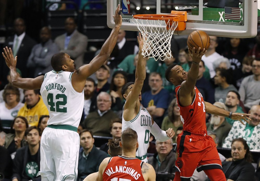 Toronto Raptors' Norman Powell, right, goes under the basket to shoot past Boston Celtics forwards Jayson Tatum and Al Horford (42) during the first quarter Sunday at TD Garden in Boston.