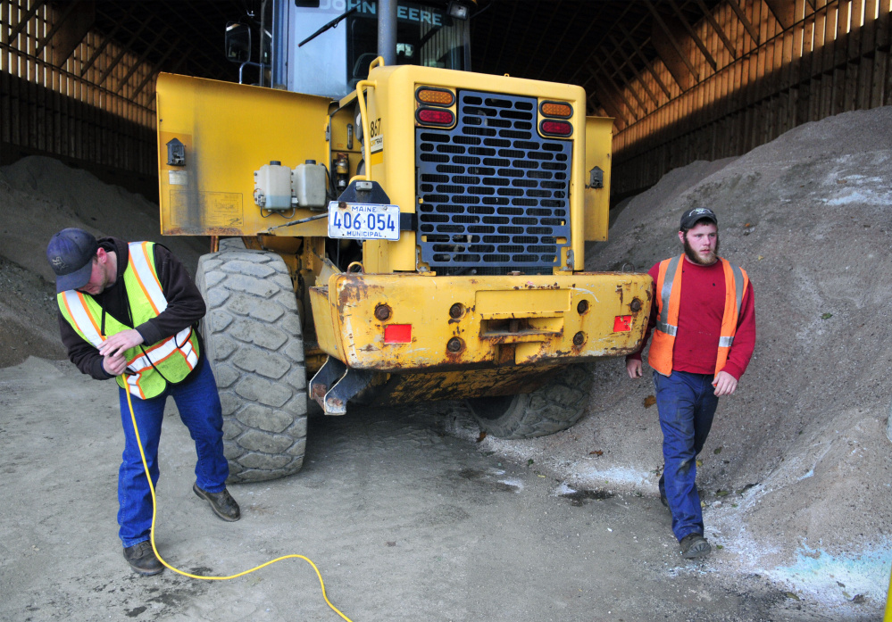 Manny Proctor cleans the sand out of the extension cord before plugging it into the block heater on front end loader that Justin Miller just moved into the salt shed on Thursday at the John Charest Public Works Facility in Augusta. The men recently got their Class B Commercial Drivers Licenses and will be driving plow trucks for the city this winter.