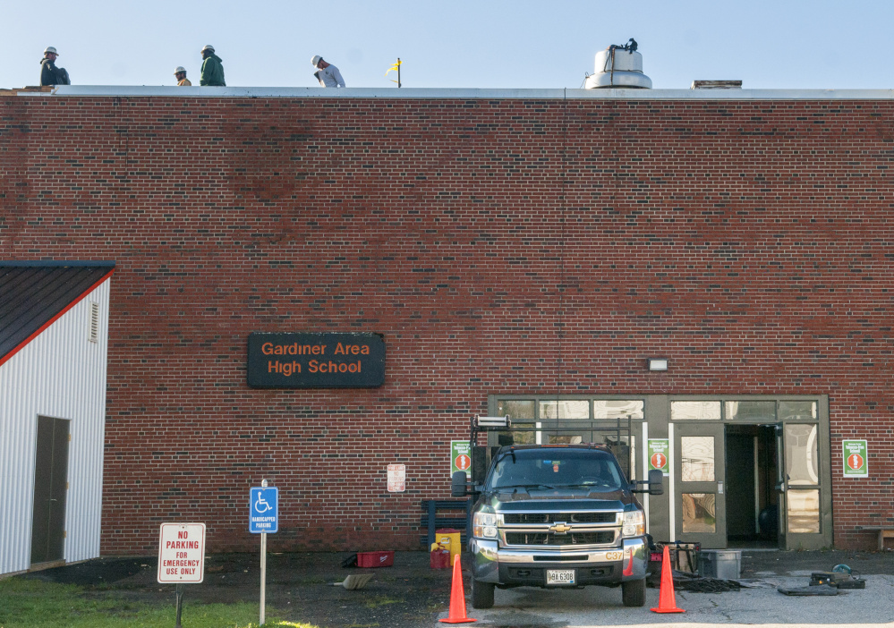 Workers from G&E Roofing tend to the wind damaged roof of the James A Bragoli Memorial Gym at Gardiner Area High School on Oct. 31.