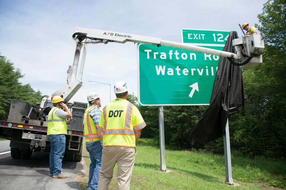 Workers with the Maine Department of Transportation unveil the sign recently for the new exit 124 off Interstate 95 connecting with Trafton Road in Waterville.