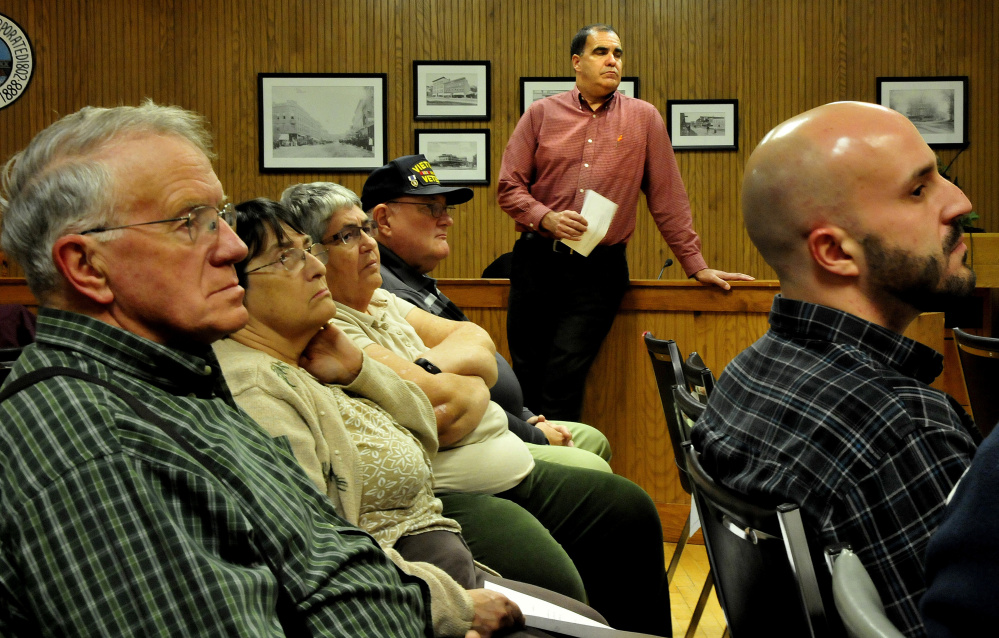 Ernie Martin, background, project manager for the Maine DOT, listens to speakers Monday during a meeting regarding the Trafton Road project at City Council in Waterville.