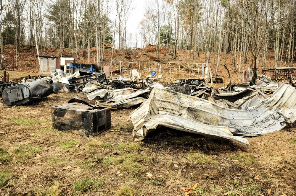 Fire destroyed this garage early Tuesday morning on Hunts Meadow Road in Whitefield. Firefighters pulled it down with an excavator to expose any remaining fire, which is why the metal roof and other items are spread around the yard.