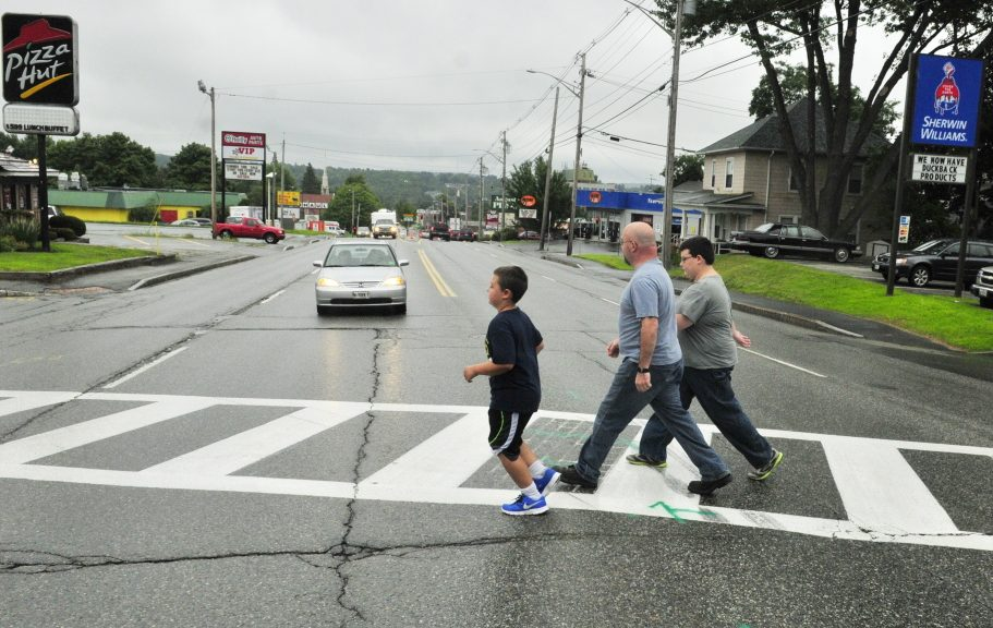 Jason Wyman, center, and his sons, Keygan, 10, left, and Ayden, 11, cross Western Avenue in Augusta in 2014 in a crosswalk where the avenue intersects with Florence and Cushman streets. A forum held Wednesday in Augusta sought comments from pedestrians and others about ways to improve safety in the city.