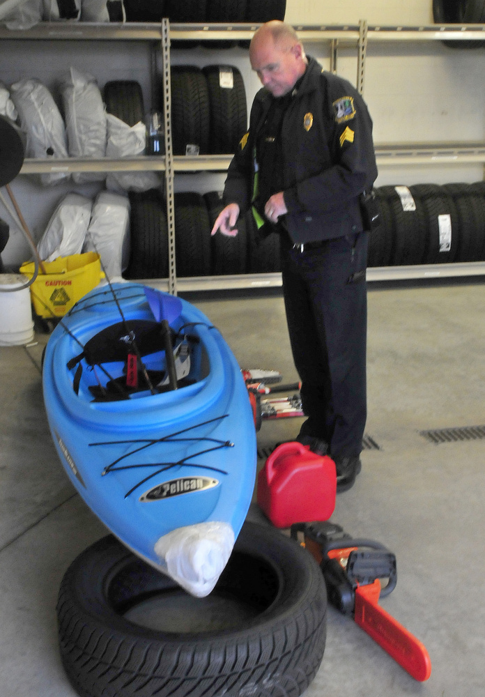 Waterville police Sgt. Alden Weigelt looks over some of the items recovered Wednesday outside the Hathaway Creative Center that had been taken sometime Sunday night from various vendors at the Sukeforth Family Festival of Trees. They include a kayak, tools, fishing equipment and a chain saw. Bobby Campbell, a transient, has been charged with burglary and theft.
