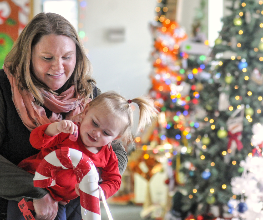 Marie Woodcock, left, holds her daughter Emma McKenna as she drops a ticket into a PVC pipe candy cane to vote for one of her favorite trees Friday at the River of Trees event in downtown Augusta.