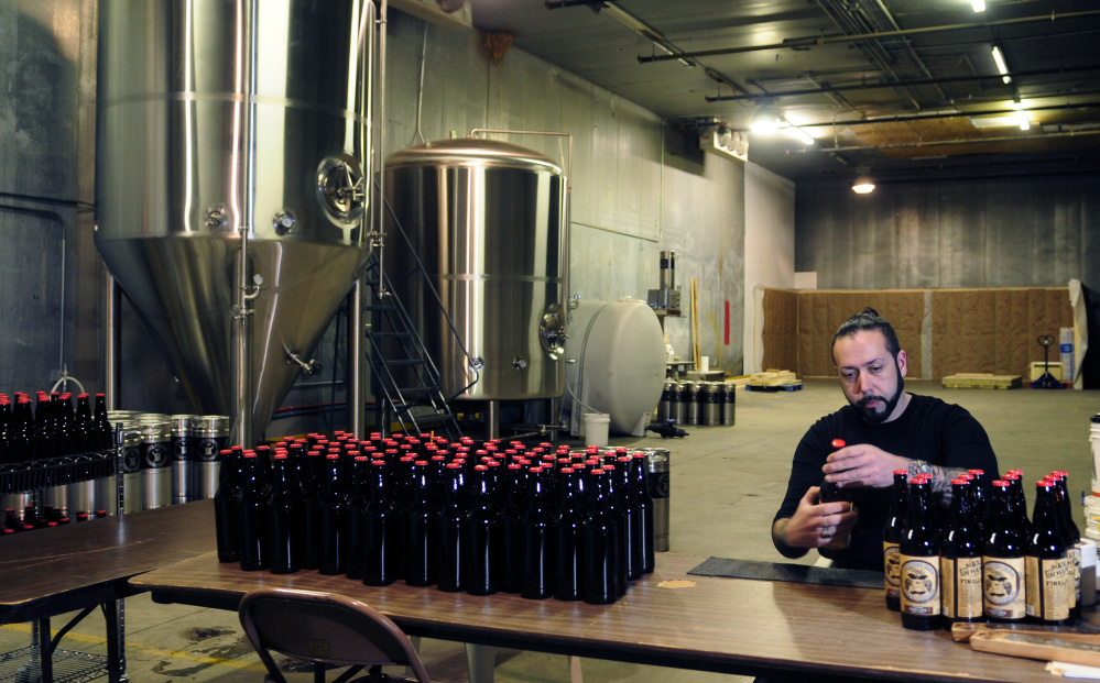 Owner David Boucher puts labels bottles at Lost Orchard Brewing Company on March 4, 2016 in South Gardiner. The facility has since closed and the former church in Gardiner that was to be used as a tasting room is up for auction.