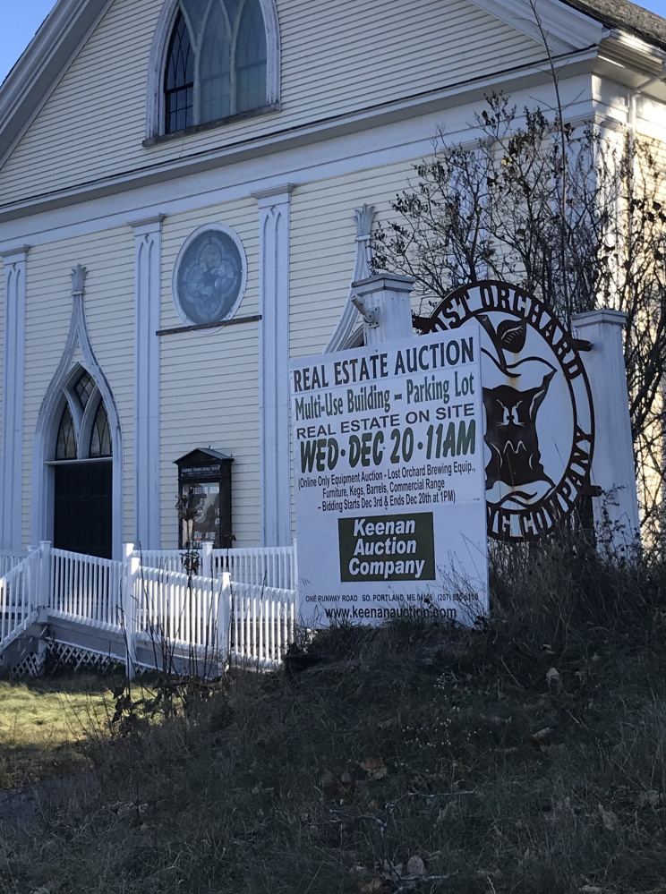 An auction sign outside Lost Orchard Brewing Company in Gardiner on Tuesday. The church is expected to be auctioned to the highest bidder on Dec. 20.