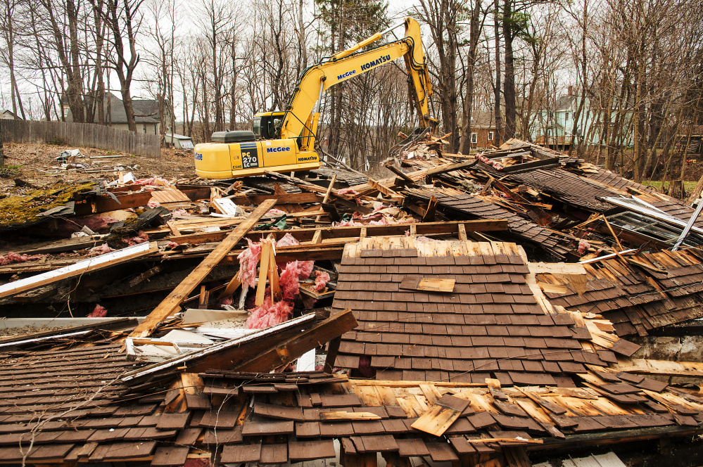 An excavator moves the demolished remains of 18 Dennis St. on April 19 in Gardiner. On Wednesday, City Council will consider whether to sell the now vacant lot to a neighbor.