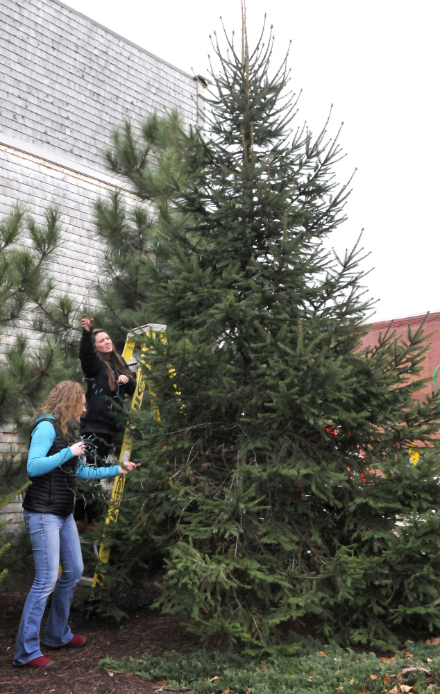 Main Street Skowhegan board member Darcy Spooner, left, and volunteer Mary Haley remove old Christmas lights from trees in the park in downtown Skowhegan before stringing new lights Wednesday for the upcoming 25th annual Holiday Stroll.