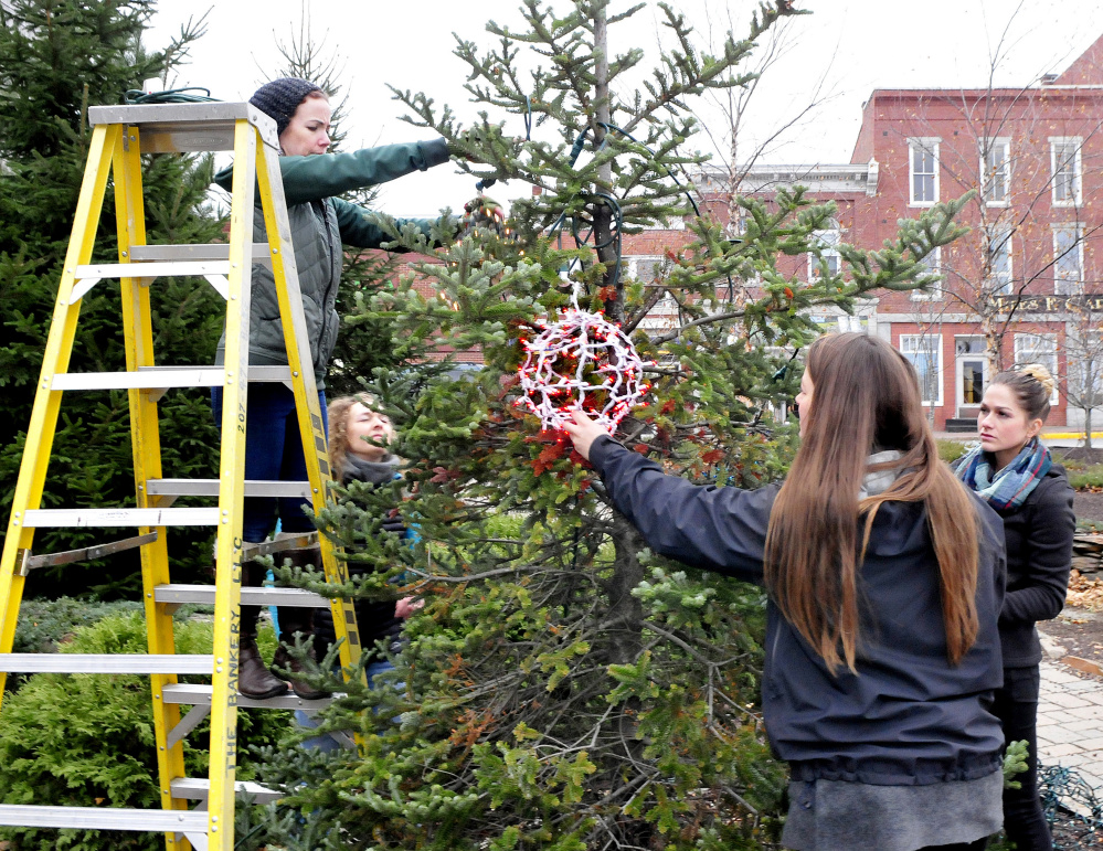 Main Street Skowhegan volunteers and board member Darcy Spooner, second from left, string hand-made balls of Christmas lights on trees Wednesday in the park in downtown Skowhegan for the upcoming 25th annual Holiday Stroll. Volunteers are, from left, Devin MacMichael, Spooner, Mary Haley and Kylie Damon.