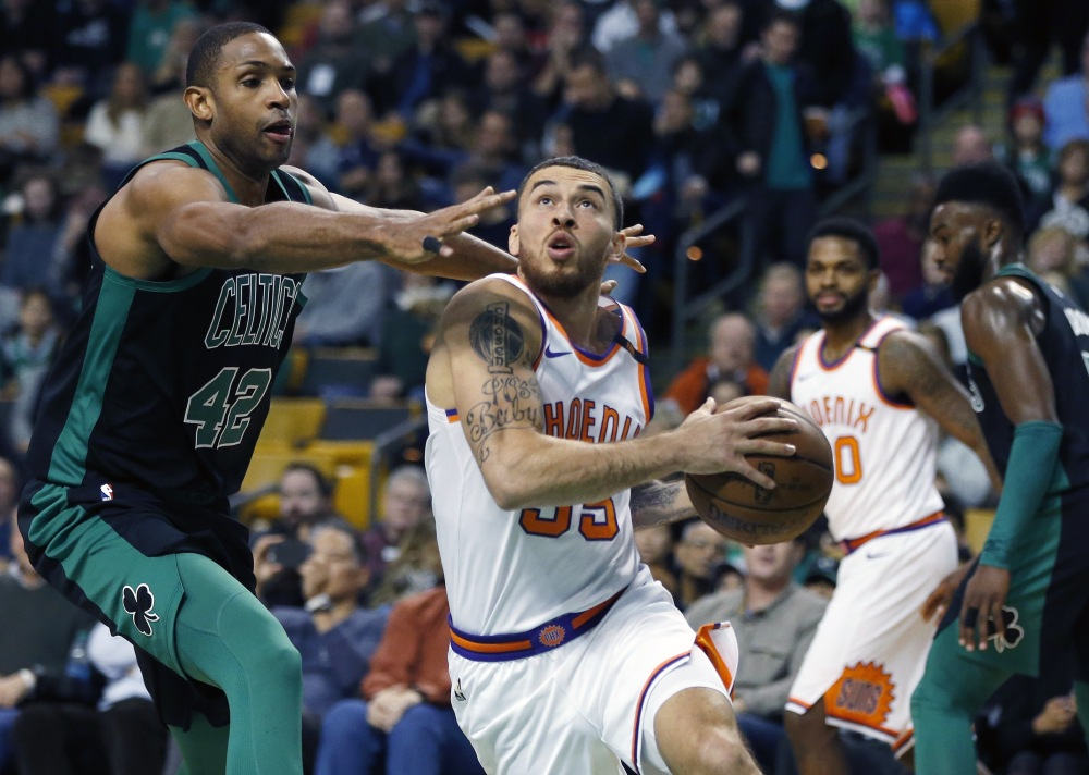 Mike James of the Suns drives past Al Horford of the Celtics during the first quarter Saturday in Boston. The Celtics held on for a 116-111 win.