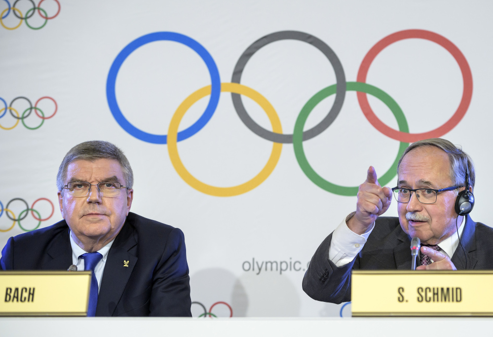 International Olympic Committee President Thomas Bach from Germany, left, and Samuel Schmid, president of the IOC Inquiry Commission and former president of Switzerland, right, comment during a news conference in Lausanne, Switzerland, on Tuesday.  Russian athletes will be allowed to compete at the upcoming Pyeongchang Olympics as neutrals despite orchestrated doping at the 2014 Sochi Games, the International Olympic Committee said.