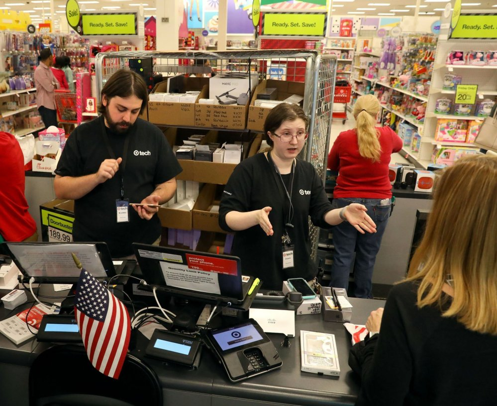 Brad Garrett, left, and Angela Johannsen help customers in the tech department of Target in Ballwin, Mo., on Tuesday, as the service sector reported its 95th month of consecutive growth.