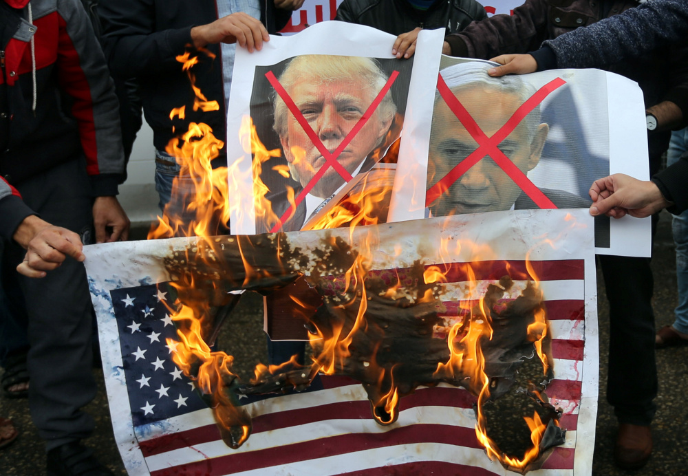 Palestinians in Rafah in the southern Gaza Strip burn posters Wednesday of Israeli Prime Minister Benjamin Netanyahu and U.S. President Trump at a protest of the U.S. intention to move its embassy to Jerusalem and to recognize that city as the capital of Israel.