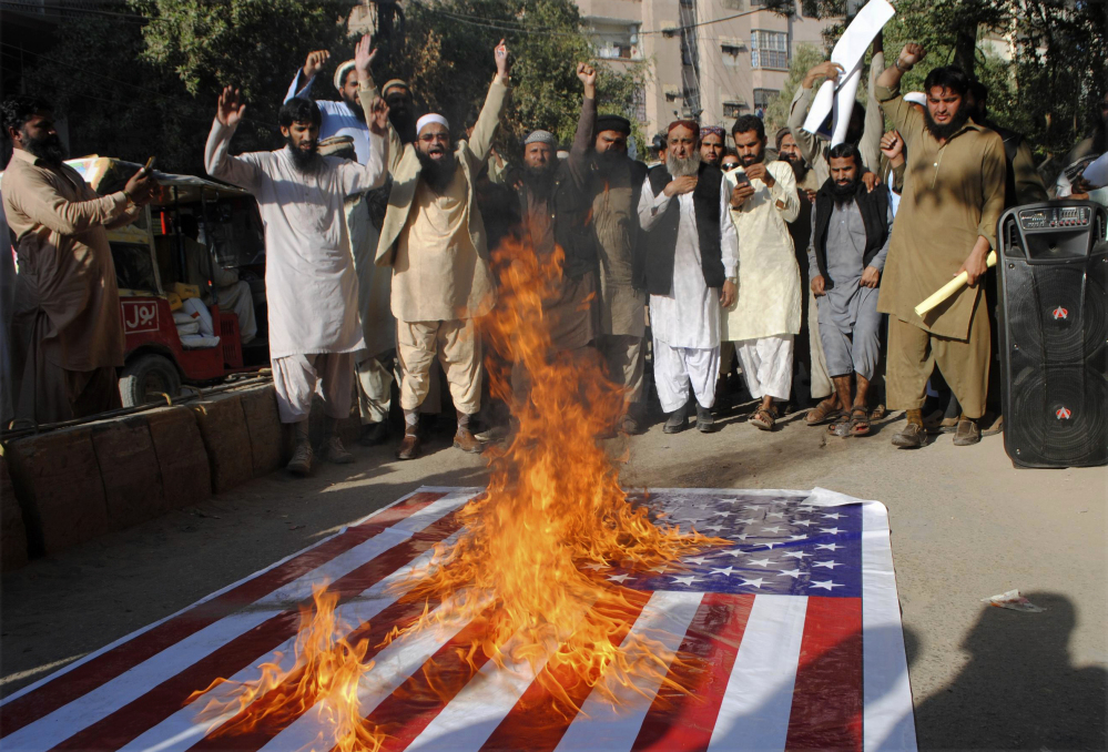 Pakistanis burn a representation of the U.S. flag during a protest rally in Hyderabad, Pakistan, Thursday. Hundreds of Islamists have rallied in major cities of Pakistan, condemning President Trump for declaring Jerusalem as Israel's capital.