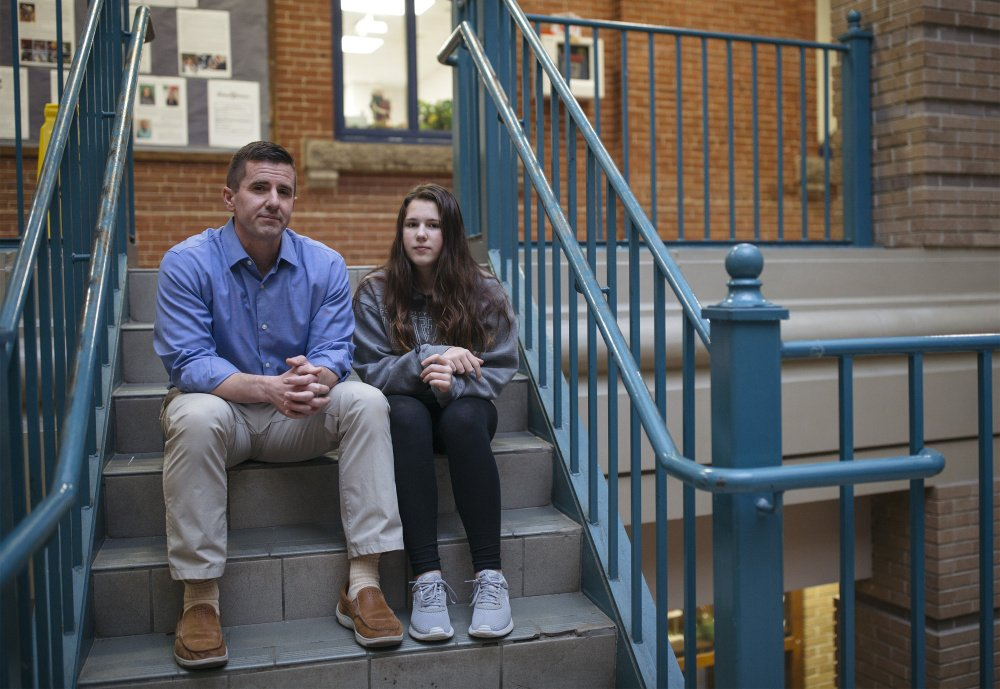 Greg Payne and his daughter Georgianna, 14, sit Thursday outside Portland High School, where she is a freshman. Years ago, when they lived in Massachusetts, a law on testing for lead spared her from severe damage.