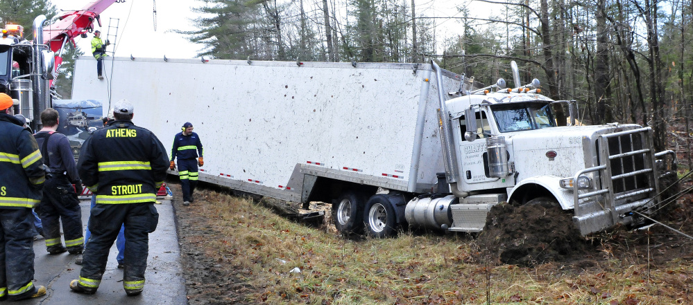 Tow truck operators work on removing this tractor-trailer carrying sawdust that overturned early Wednesday morning on Route 150 in Athens.
