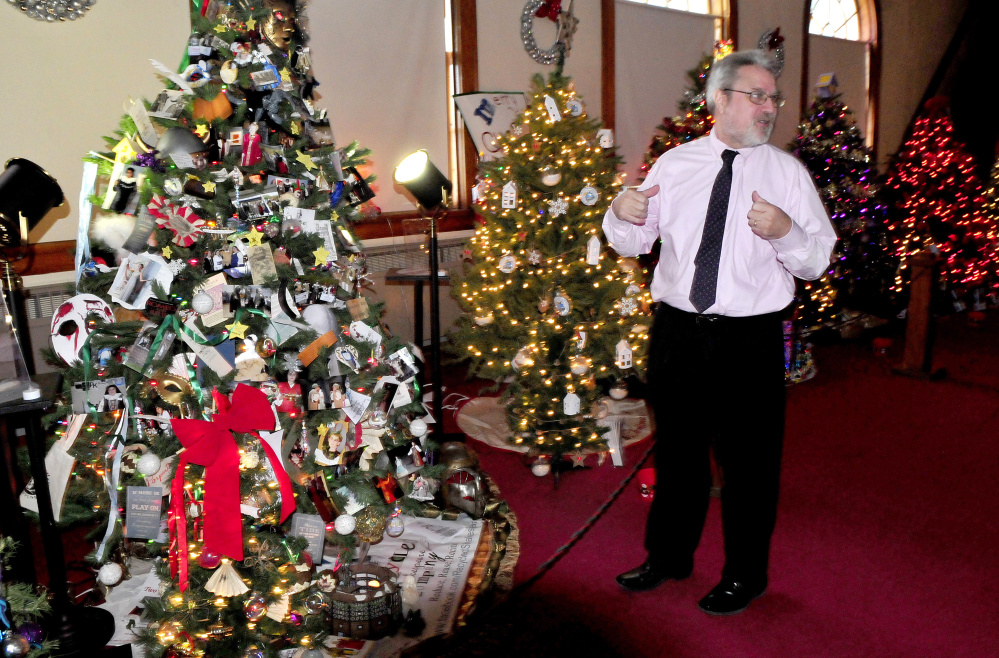 Ken Coville, president of Good Will-Hinckley, talks about the decorated Christmas trees of the many businesses and organizations that sponsored them, including the Recycled Shakespeare Company tree at left, at this year's Festival of Trees. The festival begins Friday in Prescott Hall in Fairfield and runs through Dec. 16.