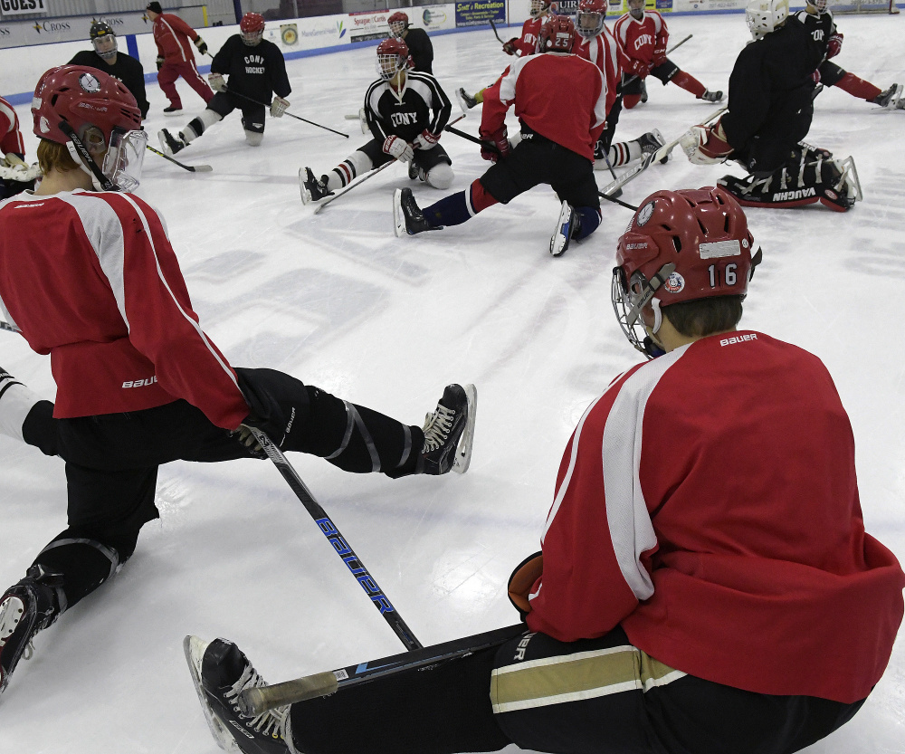 Members of the Cony/Hall-Dale/Monmouth hockey team get loose before a Nov. 28 practice in Hallowell.