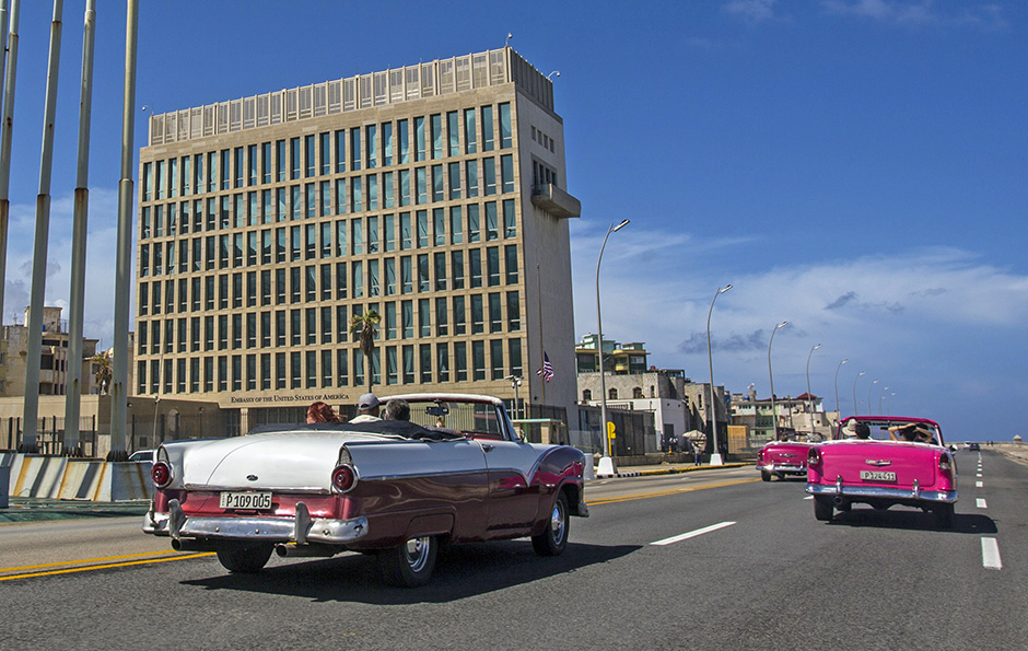 Tourists in vintage American cars pass the American Embassy in Havana in October. The U.S. says 24 embassy  officials and spouses fell ill starting last year in homes and later in some hotels.