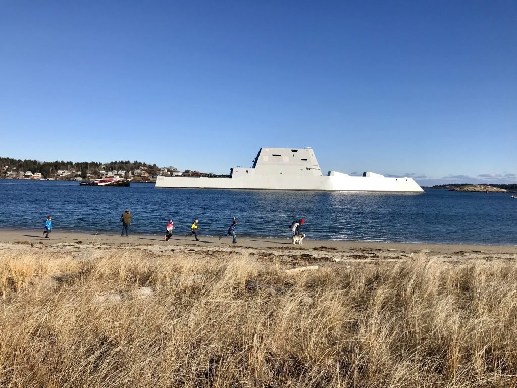 Children run on the beach near Fort Popham as BIW's new Zumwalt destroyer cruises past on its way into Sagadahoc Bay on Monday afternoon.