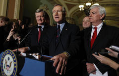 Senate Majority Leader Harry Reid of Nev., center, answers questions outside of the Senate chambers on Capitol Hill in Washington, Thursday, Dec. 24, 2009, after the Senate passed the health care reform bill. From left are, Senate Finance Finance Committee Chairman Sen. Max Baucus, D-Mont., Reid, Senate Majority Whip Richard Durbin of Ill., and Senate Banking Committee Chairman Sen. Christopher Dodd, D-Conn..