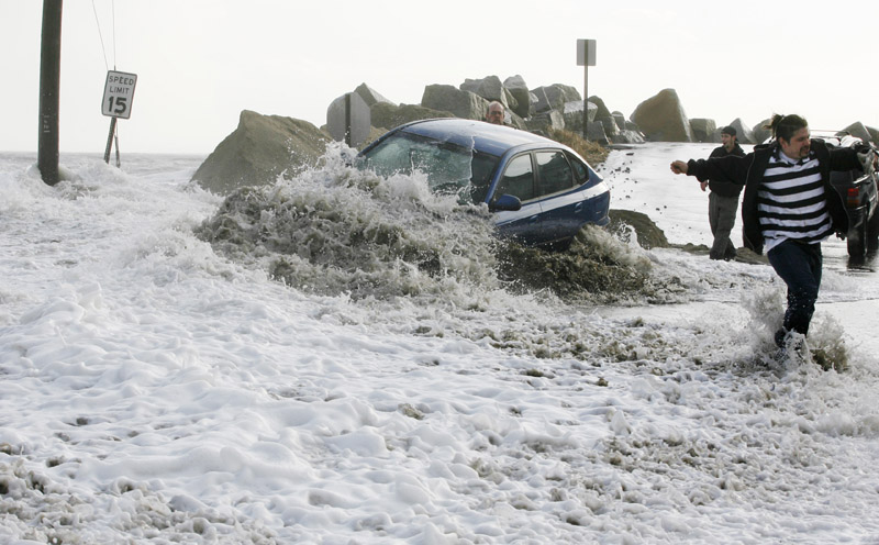 a wave breaks over an occupied car as people attempt to tow it to safety Friday at Camp Ellis in Saco. The driver left the car as the tide rose and flooded local streets.