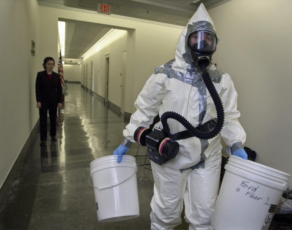 In this Nov. 6, 2001, AP file photo, biohazard worker Michelle Gillie, right, prepares to enter the office of Rep. Mike Pence, R-Ind., in the Longworth House office building on Capitol Hill in Washington. At left is Michelle Richman, scheduler for Rep. Grace Napolitano, D-Calif.