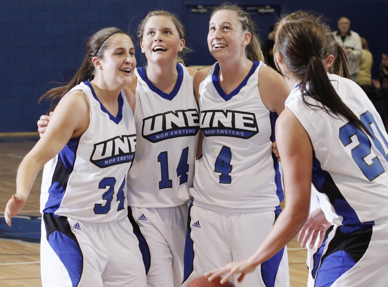 University of New England players, from left, Chelsey Meszaros, Kelley Paradis, Carrie Bunnell and Margo Russell begin to celebrate as the clock winds down on their win over Regis in the Commonwealth Coast Conference final.