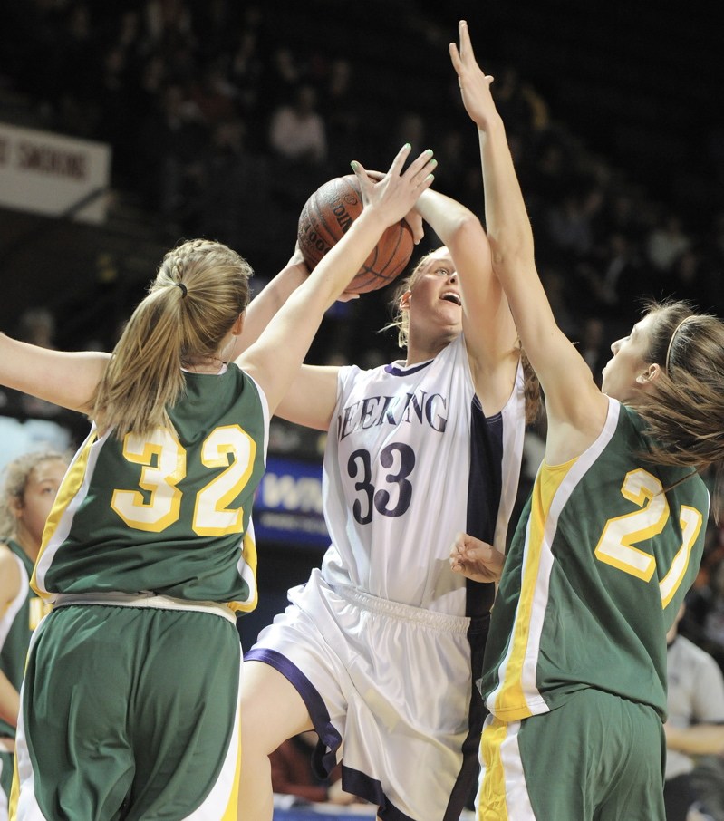 Kayla Burchill, who scored 19 points for Deering, looks to drive against Chantalle Desjardins, left, and Alexa Coulombe of McAuley during their Western Class A semifinal. Deering won, 45-35.