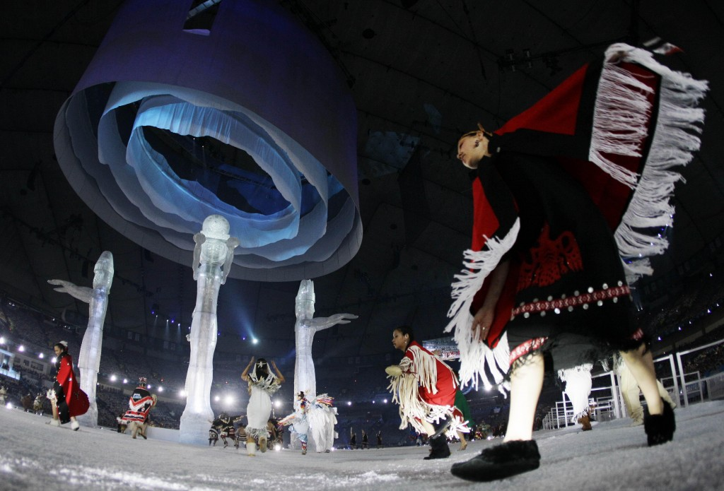 Aboriginal people of Canada dance around Welcoming Poles during the opening ceremony for the Vancouver 2010 Olympics in Vancouver, British Columbia, Friday, Feb. 12, 2010. (AP Photo/Gerry Broome)