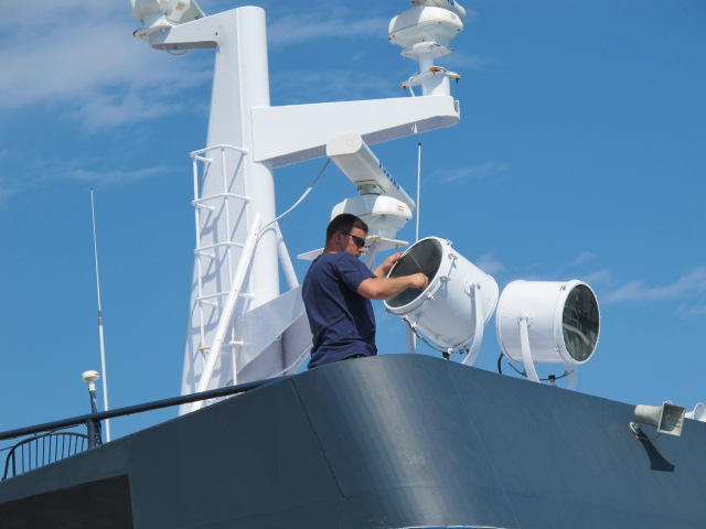 Crew member Shawn Jordan of Portland cleans the Sea Hunter's search lights Monday in anticipation of today's hoped-for departure to Haiti.