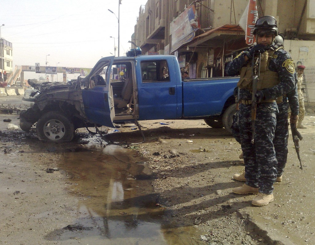 Iraqi policemen inspect the site of a bombing in Ramadi, 70 miles (115 kilometers) west of Baghdad, Iraq, Thursday, Feb. 18, 2010. A suicide car bomb exploded outside the gate of the main government compound in the capital of Iraq's Anbar province, killing at least 13 people, including four police, a health official said. (AP Photo)