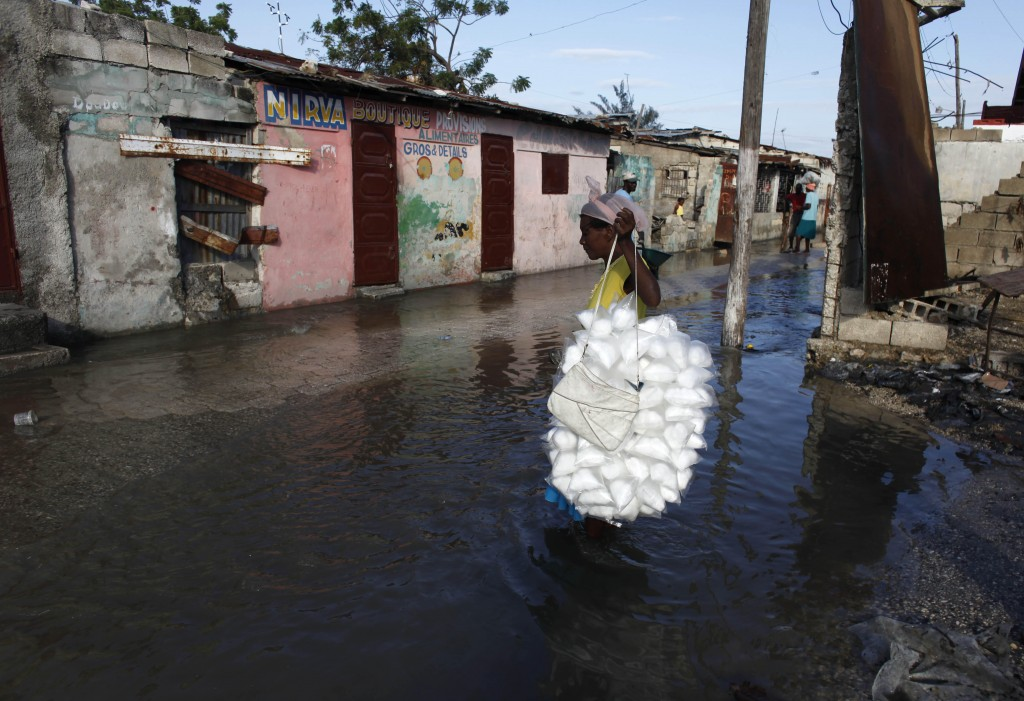 A woman carries cotton candy through a flooded street caused by heavy rains overnight in the Cite Soleil neighborhood of Port-au-Prince, Thursday Feb. 18, 2010. The capital city of Haiti is particularly vulnerable to rains at this moment as it recovers from the heavy damage it suffered during last month's earthquake. (AP Photo/Javier Galeano)