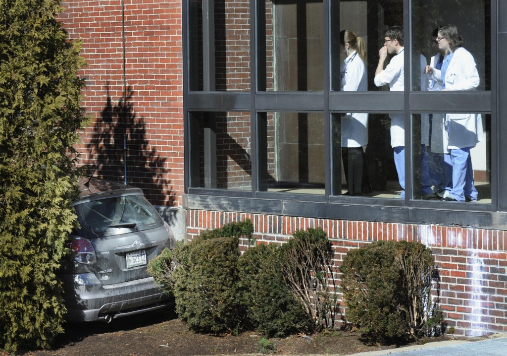 Maine Medical Center employees look at a car that crashed into a hospital building in Portland on Friday. A driver was transported to Maine Medical Center, but her condition was undetermined.