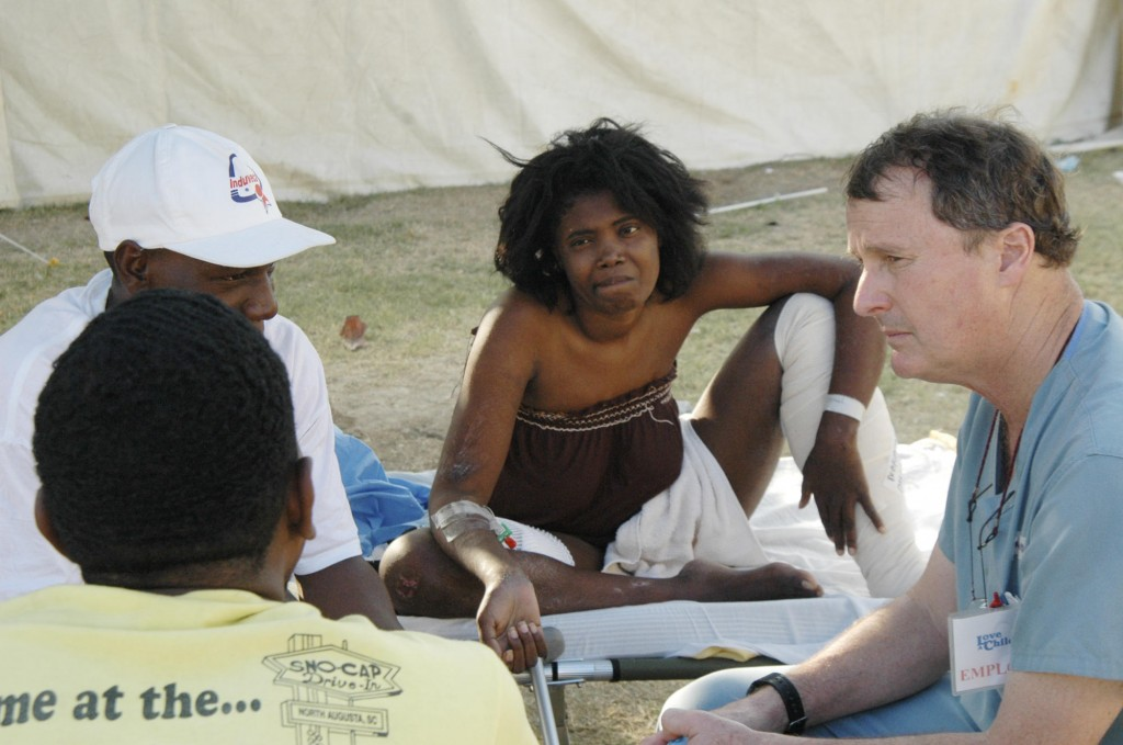 Dr. David Fitz, right, a Portland surgeon, consults with a Haitian woman and her family about the necessity of amputating her leg, at a makeshift hospital set up by the Harvard Humanitarian Initiative at an orphanage in Fond Parisien.