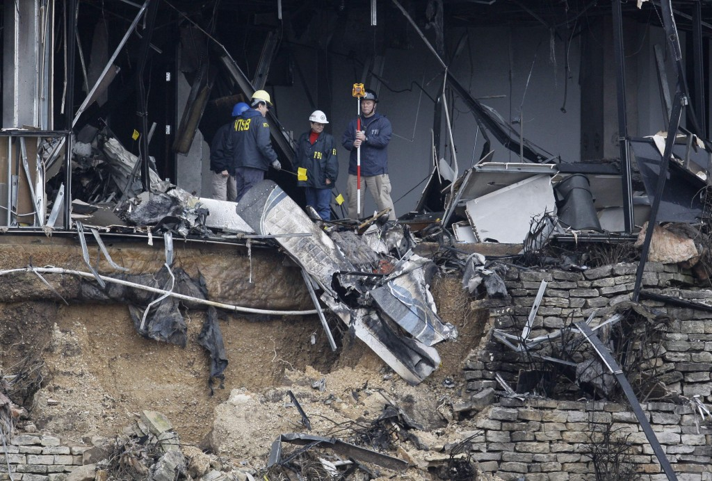 Federal investigators search through the aircraft wreckage inside a building in Austin, Texas, on Friday. Officials said that Joseph Stack flew his plane into the building Thursday, where IRS employees worked, killing himself and one person inside.